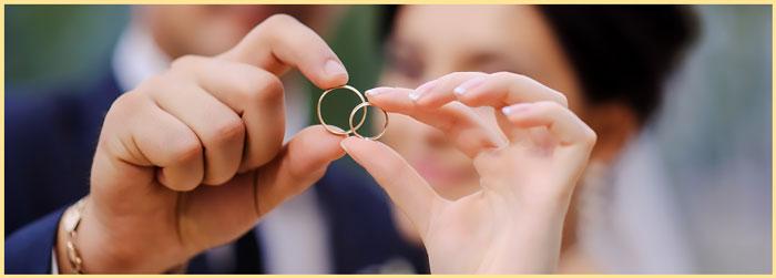 Молодожены держат в руках кольца