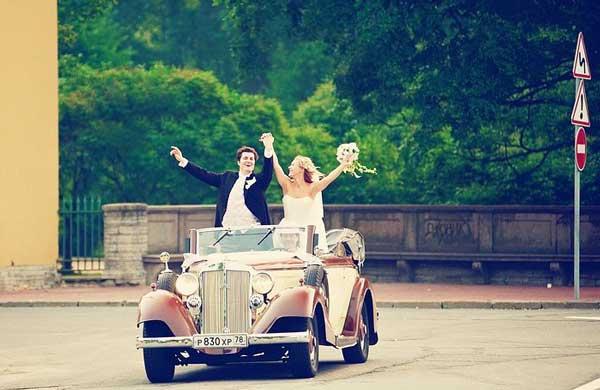 Жених и невеста едут стоя в кабриолете