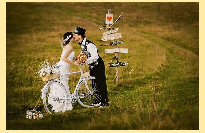 Молодожены в поле с велосипедом