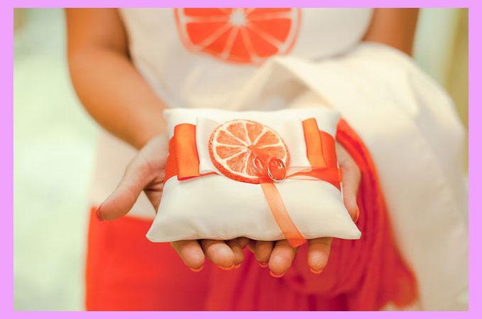 Подушечка с рисунком апельсиновых долек и кольца свадебные